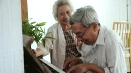 Happy senior couple playing piano at home
