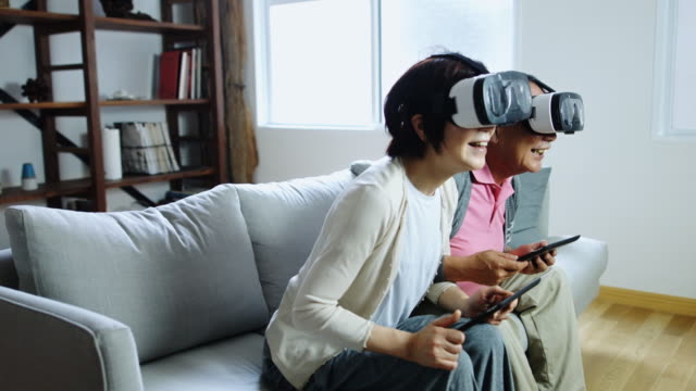 happy senior couple playing with virtual reality goggles - japan videos stock videos and b-roll footage