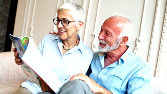 happy senior couple reading a magazine. - magazine publication stock videos & royalty-free footage