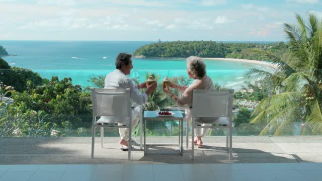 happy senior couple relaxing on balcony,4k - balcone video stock e b–roll
