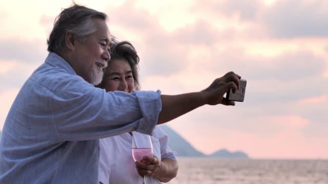 stockvideo's en b-roll-footage met gelukkige senior paar nemen selfie op strand. senior koppel ontspannen door de zee op een zonnige dag, senior vakantie, vakanties, technologie - zelfportret fotograferen