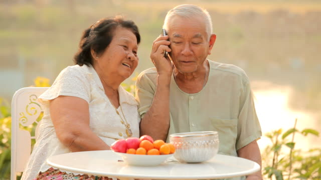 Happy senior couple talking on a mobile phone