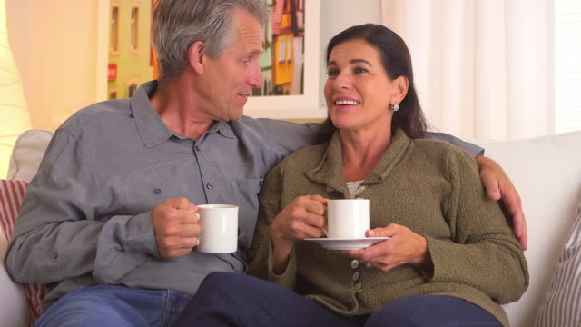 Happy senior couple talking on couch