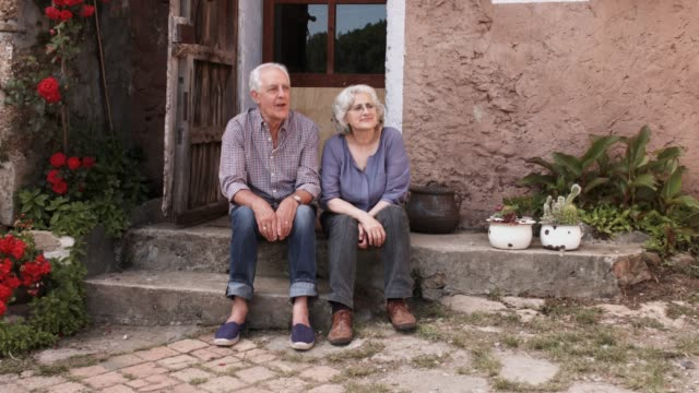 happy senior couple talking while sitting on porch - veranda stock videos & royalty-free footage