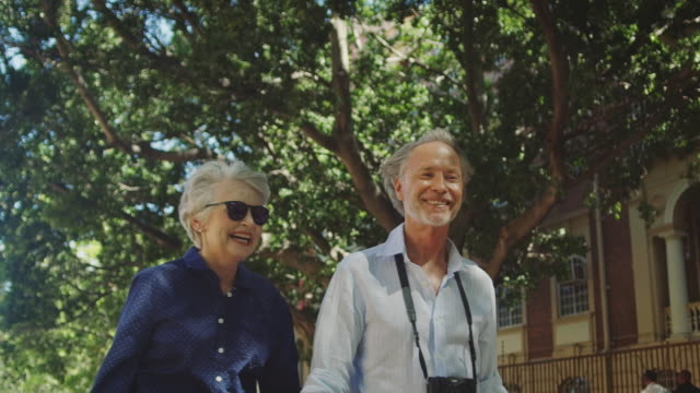 happy senior couple talking while walking in city - senior adult stock videos & royalty-free footage