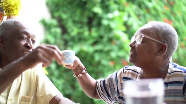 glückliches seniorenpaar toasting mit kaffeetasse - brasilianischer abstammung stock-videos und b-roll-filmmaterial