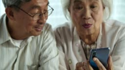Happy senior couple using smartphone and relaxing together at home