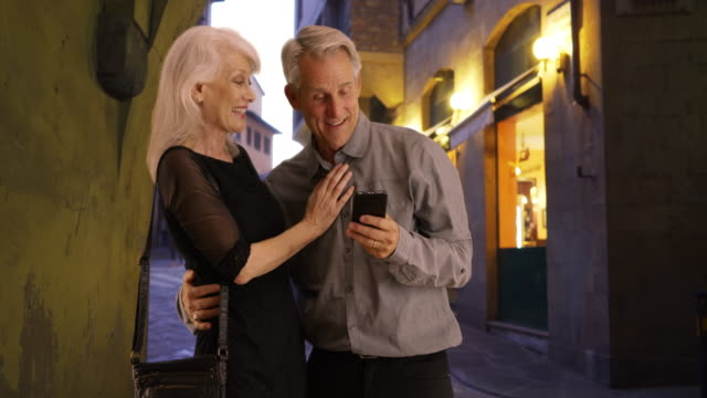 happy senior couple using smartphone on florence street - aktiver senior stock-videos und b-roll-filmmaterial
