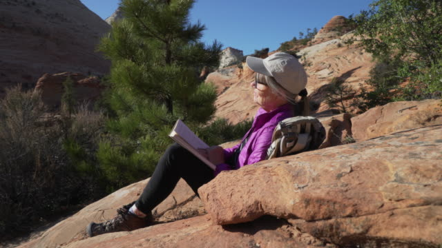 happy senior female camper sitting outdoors on sandstone canyon reading a book - letteratura video stock e b–roll