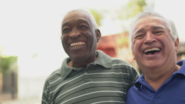 happy senior friends talking on the street - mixed race person stock videos & royalty-free footage
