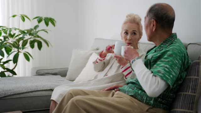 glücklich senior japanisches paar genießen kaffee auf dem sofa - angesicht zu angesicht stock-videos und b-roll-filmmaterial