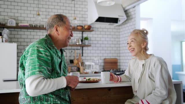 キッチンで楽しむ幸せなシニア日本人カップル - ペア点の映像素材/bロール