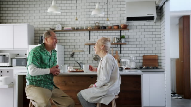 happy senior japanese couple enjoying in the kitchen - simple living stock videos & royalty-free footage
