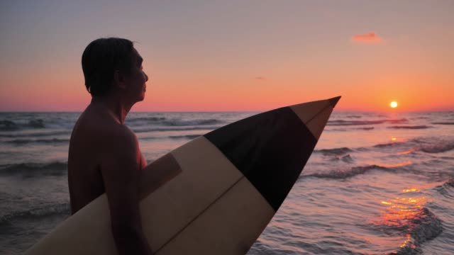 happy senior male surfer walking with surfboard on the beach during sunset.real bodies - surfboard stock videos & royalty-free footage