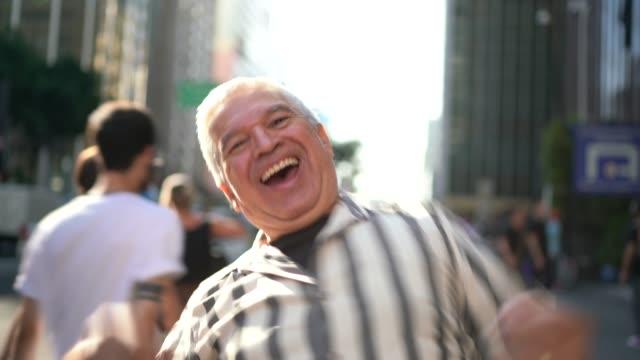 happy senior man dancing in an avenue - senior men stock videos & royalty-free footage