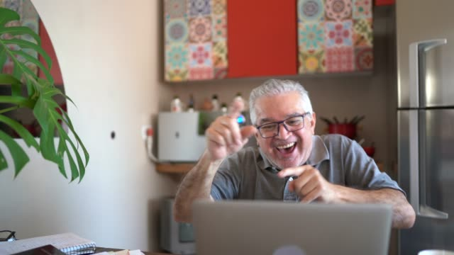 happy senior man dancing while looking to laptop at home - cool attitude stock videos & royalty-free footage