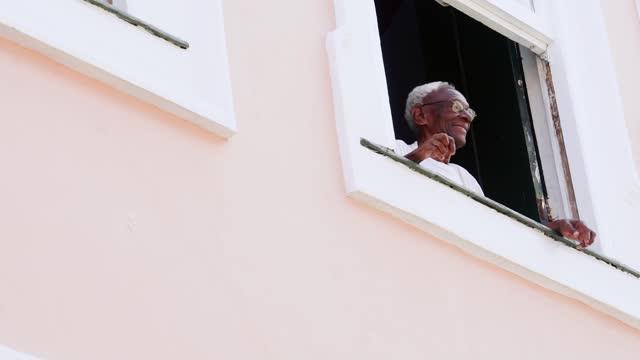 vidéos et rushes de homme aîné heureux saluant quelqu'un de son balcon de maison - saluer de la main