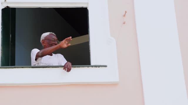vídeos de stock, filmes e b-roll de feliz idoso cumprimentando alguém da varanda de sua casa - individuality