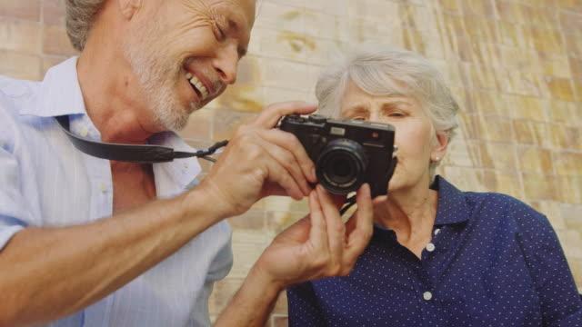 vidéos et rushes de heureux homme senior montrant appareil photo numérique pour femme - jeune d'esprit