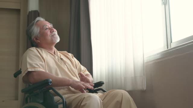 happy senior man sitting on wheel chair in hospital ward - examination gown stock videos & royalty-free footage