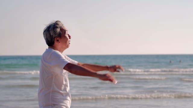 幸せなシニア男性は、ビーチで運動を引退します。日没のビーチの休暇でストレッチ体操をしているシニア男性。リアルボディ - 映像撮影点の映像素材/bロール