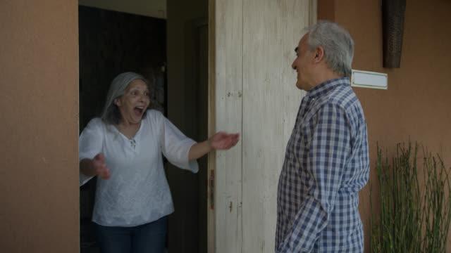 幸せなシニア男性は、彼女が喜んで開いている間、彼女のドアをノックする女性パートナーを驚かせる - 建物入口点の映像素材/bロール