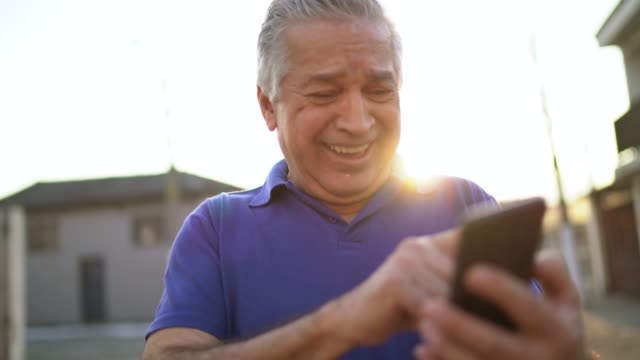 happy senior man using phone on the street - senior men stock videos & royalty-free footage