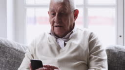 Happy senior man using smart phone relaxing on couch