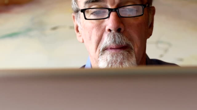 happy senior man using technology - looking at computer monitor stock videos & royalty-free footage