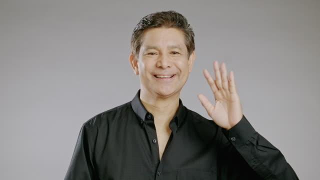 happy senior man waving left hand. - black shirt stock videos & royalty-free footage