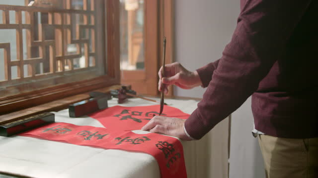 happy senior man writing calligraphy on couplets,4k - calligraphy stock videos & royalty-free footage