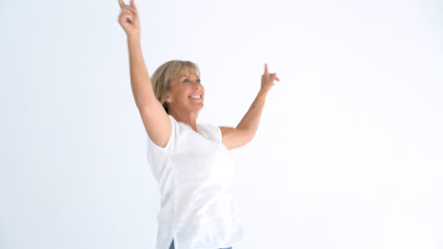 Happy senior woman celebrating with arms raised