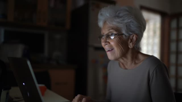 happy senior woman doing a video call at home - grandparent stock videos & royalty-free footage