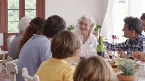 vídeos y material grabado en eventos de stock de feliz mujer mayor disfrutando con la familia en la mesa - plato de comida