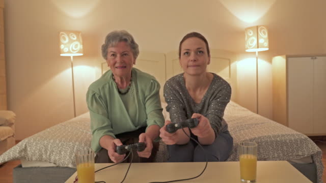 Happy senior woman having fun and celebrating while playing video game with her adult daughter at home.