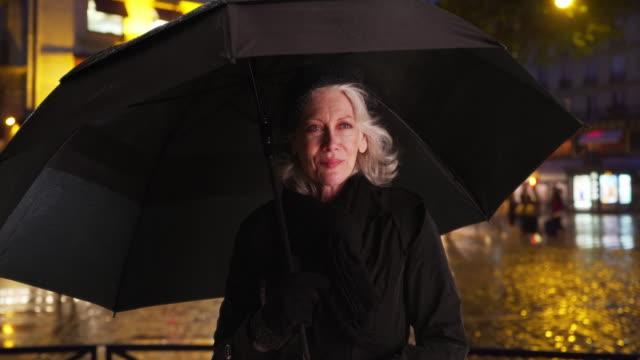 vídeos y material grabado en eventos de stock de happy senior woman in paris smiling under umbrella on rainy night in the city - abrigo de invierno