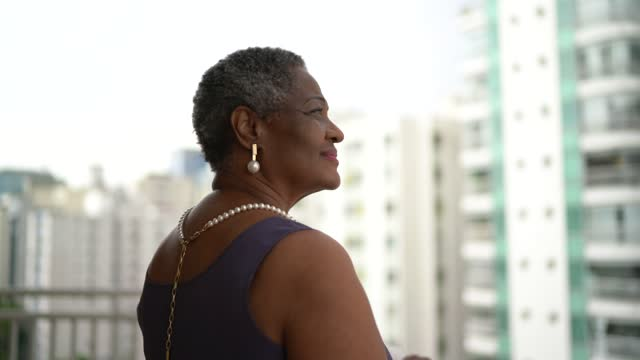 happy senior woman looking at view in apartment's porch - looking away stock videos & royalty-free footage