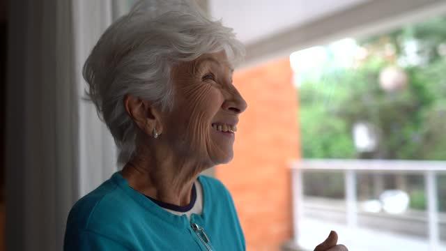 stockvideo's en b-roll-footage met gelukkige hogere vrouw die weg kijkt en thuis overweegt - schizofrenie