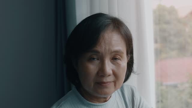 vidéos et rushes de bonne femme senior potrait. femme âgée asiatique regardant la caméra, souriant. - victime
