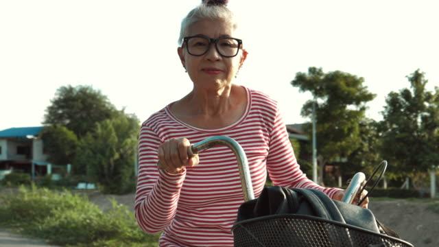 happy senior woman riding bicycle - grey hair stock videos & royalty-free footage
