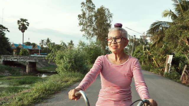 vidéos et rushes de bicyclette d'équitation supérieure heureuse de femme - grand mère
