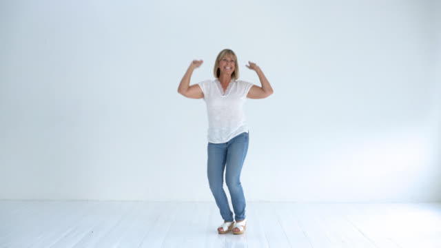 Happy senior woman smiling and jumping up and down