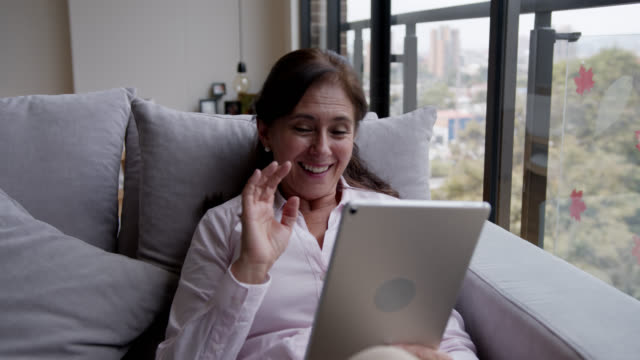 vidéos et rushes de femme aînée heureuse restant en sécurité à la maison sur une vidéoconférence utilisant une tablette - rester à la maison expression