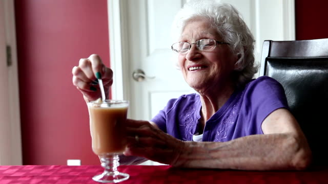 happy senior woman stirring tea - dentures stock videos and b-roll footage