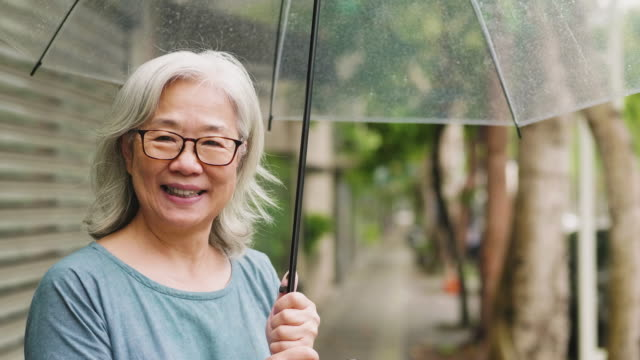A happy senior woman with an umbrella on a rainy day in the city