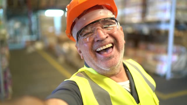 vidéos et rushes de travailleur aîné heureux prenant un selfie à l'entrepôt - selfie