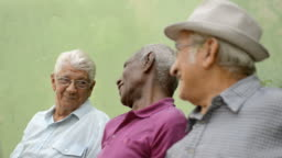 Happy seniors, old men laughing and talking in city park