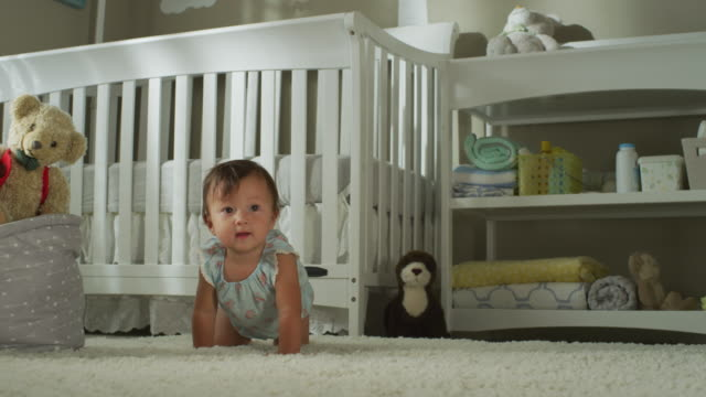 a happy seven-month-old asian baby with dark eyes, dressed in a simple cover, sits, then crawls in front of her crib, toward camera. - 生後6ヶ月から11ヶ月点の映像素材/bロール