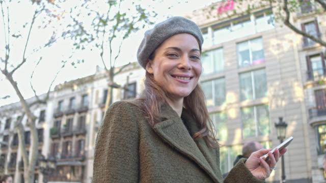vidéos et rushes de femme heureux accro du shopping à l'aide de téléphone intelligent shopping autour de la ville - shopaholic