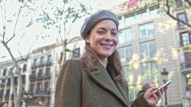 happy shopaholic woman using smart phone shopping around the city - shopaholic stock videos & royalty-free footage